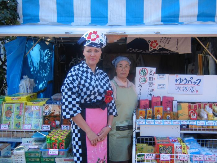 NHK TV reporter Judit Kawaguchi with a shop clerk on Izu Oshima island in Japan. Judit is dressed in the outfit worn for the island's camellia festival, called the Izu Oshima Tsubaki Matsuri.
