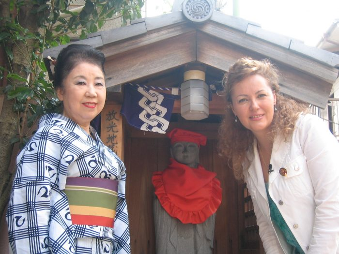 Folk musician Suzue Akashi and journalist Judit Kawaguchi with a statue of Ojizo-sama.