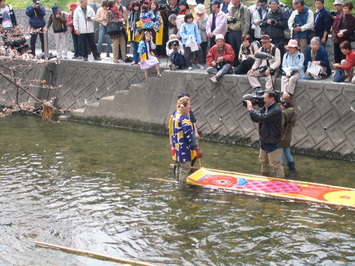 Judit Kawaguchi in the river washing the koinobori that was just freshly painted