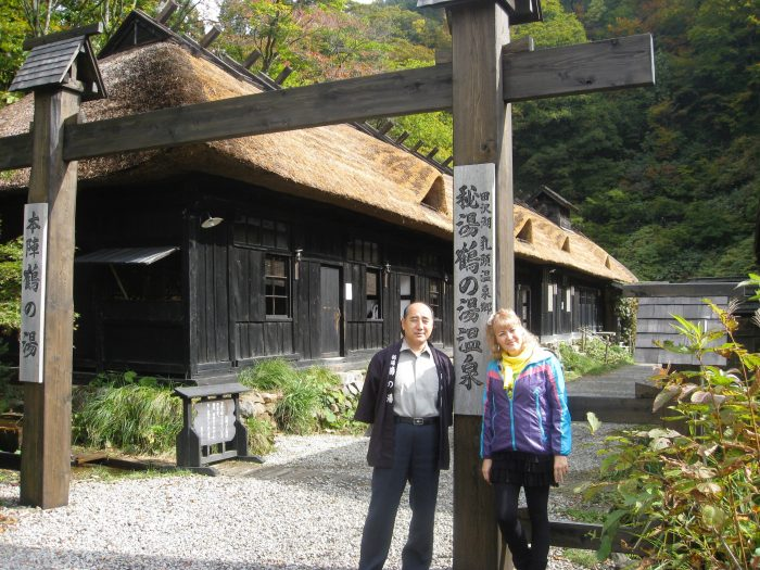 Kazushi Sato, owner of Tsurunoyu onsen and TV reporter Judit Kawaguchi at the entrance to the hotel